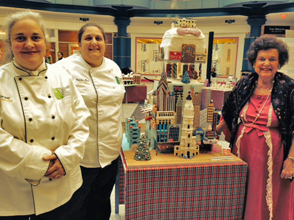 Julia Quay and Francine Marz. from the Culinary Arts Institute of Montgomery County Community College creators of the Laurel Hill Mansion Gingerbread House with the chairwomen of the board of Women for Greater Philadelphia, Alma Jacobs