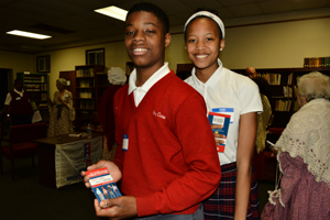 "Two students showing off ""What it says, What it Means"" a pocket guide to the constitution which was donated by Rawle and Henderson and given to all the student participants."