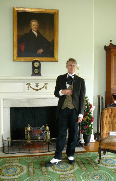 Fairmount Park guide Tyson Gardner in period costume stands in front of a portrait of William Rawle that hangs in Laurel Hill Mansion.