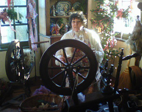 Photograph of a woman in colonial costume with spinning wheels